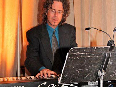 Jay Lemon playing the keyboard while dressed in a suit